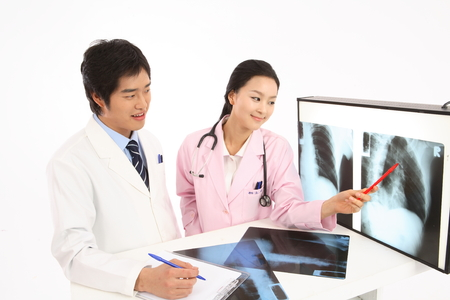 A male doctor and a female doctor in discussion as looking at x-ray photographs on screen Stock Photo