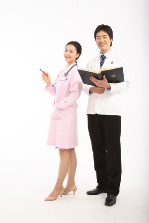 Full shot of A male doctor holding a book standing next to the female doctor in a pink robe Stock Photo