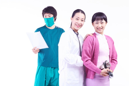 A male surgeon wearing a surgical mask holding a patient chart as standing next to the female doctor and nurse