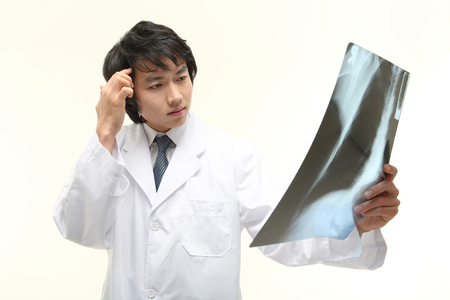 figuring: Close up shot of A male doctor thinking deeply as holding an x-ray photograph Stock Photo