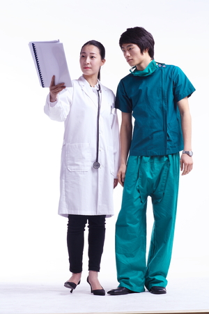 Full shot of A male surgeon and a female doctor looking at a patient chart together
