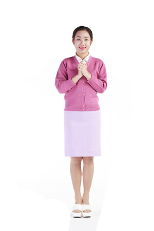 Full shot of A female hospital coordinator holding hands together in front of the chest with a toothy smile Stock Photo