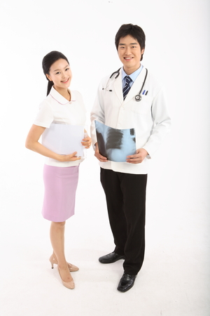 Full shot of A male doctor holding an x-ray photograph next to the female doctor holding a patient chart