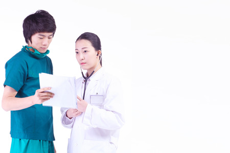 md: A male surgeon and a female doctor looking at a patient chart together