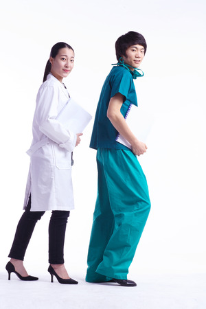 Full shot of A male surgeon and a female doctor in walking motion as holding charts each Stock Photo