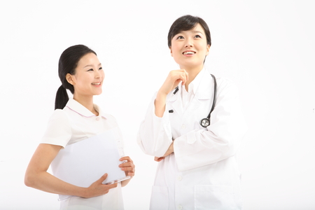Close up shot of A female doctor and nurse holding a patient chart together Stock Photo