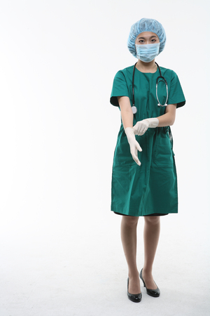 Full shot of A female surgeon putting on surgical gloves as wearing surgical gown, mask and head cap Stock Photo