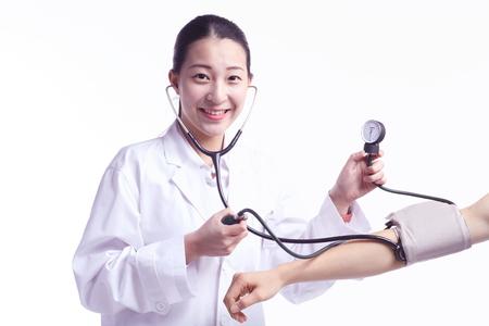 Geïsoleerd schot van een vrouwelijke arts die de bloeddrukmeter en de stethoscoop met behulp van