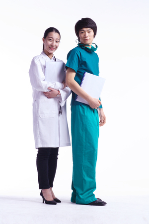Full shot of A male surgeon and a female doctor holding charts standing in a row