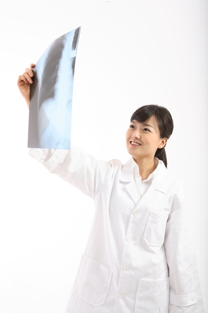 A female doctor looking at an x-ray photograph as holding it in one hand Stock Photo