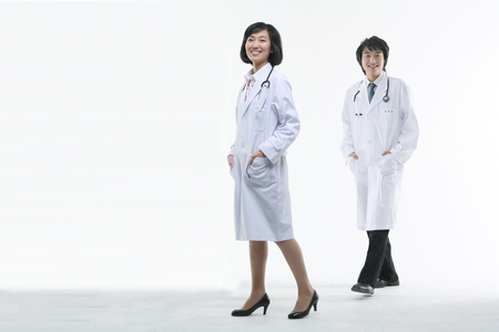 Full shot of A couple of doctors in walking motion as putting hands in pocket Stock Photo