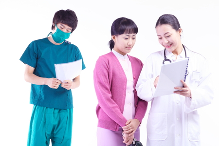 ortopedia: A female doctor, nurse and a male doctor looking at a patient chart together
