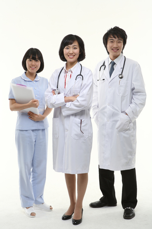 Two doctors and a nurse standing with toothy smile as crossing arms