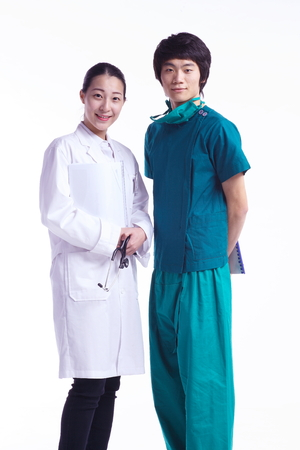 A female doctor holding a patient chart in arms while the male surgeon holding a chart behind the back