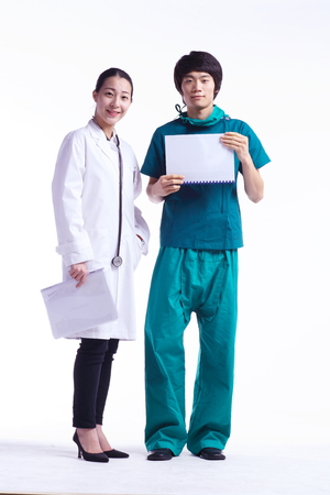 Full shot of A male surgeon and a female doctor holding charts standing next to each other Stock Photo