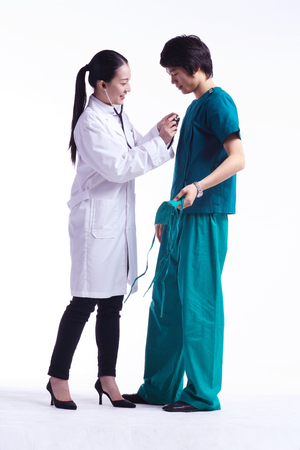 md: Full shot of A female doctor applying the stethoscope on the male surgeon in surgical suit