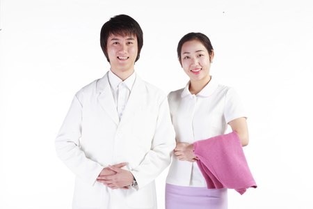 Close up shot of A male doctor standing next to the female nurse holding a jacket in arm