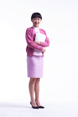 Full shot of A female nurse in pink uniform holding a patient chart in arms Stock Photo
