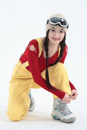 knee boots: A female skier tying shoelace of ski boots as kneeling down on one knee
