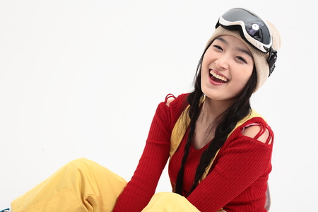 Close up shot of A female snowboarder sitting with legs up with toothy smile