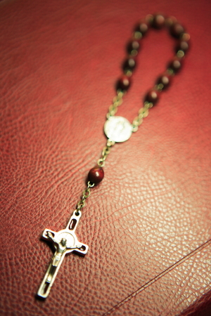 Close up shot of a small brown rosary laid on the leather covered desk