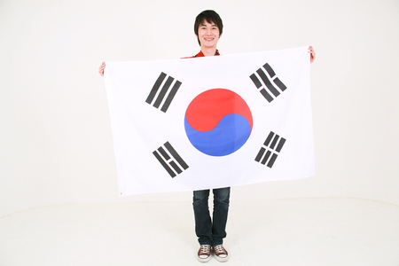 Full shot of A male Korean holding the national flag of Korea in front of himself