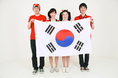 Two girls and boys of Korean soccer supporters holding the national falg of Korea Stock Photo