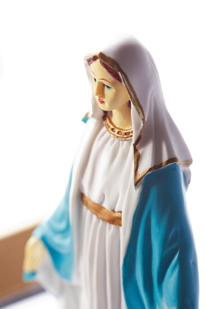 Table statue of Virgin Mary with the bible opened and mass veil laid around