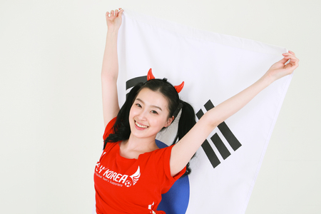 A female Korean with hair in two ponytails holding the national flag of Korea with raised arms