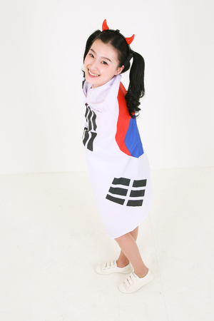 A female Korean with hair in two ponytails covering herself with the national flag of Korea