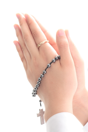 Isolated shot of praying hands with a rosary in hands of A female Asian