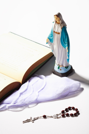 Talbe statue of Virgin Mary with the bible and rosay laid around Stock Photo