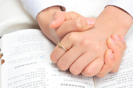 Isolated shot of an aisan womans praying hands on the open bible