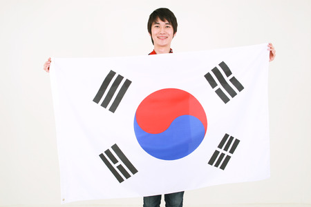 Close up shot of A male Korean holding the national flag of Korea in front of himself Stock Photo
