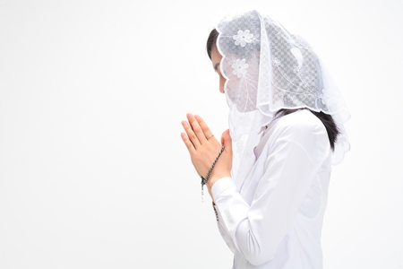 Side shot of A female Asian wearing a mess veil praying with a rosary in hand