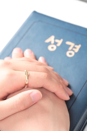 fingers put together: Isolated shot of a female Asians hands with a rosary ring laid on the closed bible together