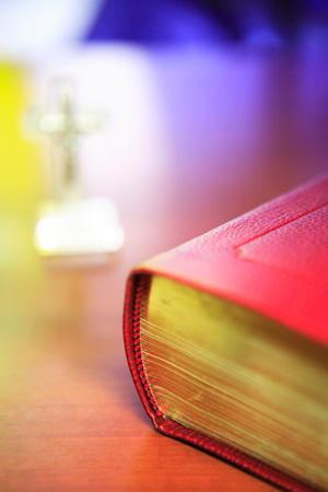hallowed: Close up shot of the closed bible laid on the desk with a table cross in background Stock Photo