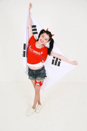 Full shot of A female Korean with hair in two ponytails holding the national flag of Korea with raised arms