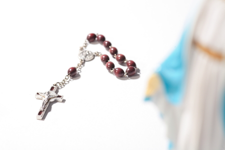 Isolated shot of the cross of rosary behind the table statue of virgin Mary