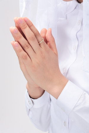 Isolated shot of praying hands with a rosary ring of A female Asian weraing white mass veil