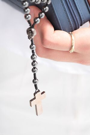 Isolated shot of a female Asians hands with a rosary ring holding the bible and rosary tightly
