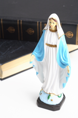 Table statue of Virgin Mary with the bible laid around