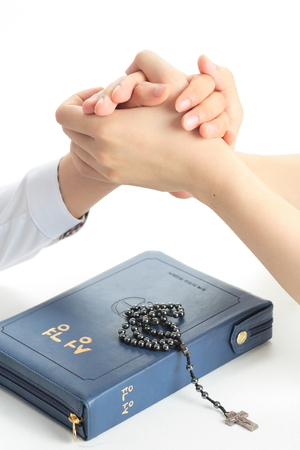 Isolated shot of A female Asians praying hands as holding the others hands together on the bible
