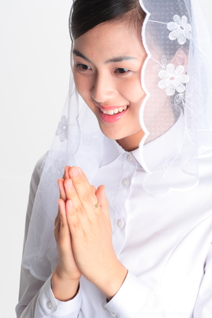 Close up shot of A female Asian wearing a mass veil praying with toothy smile