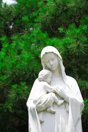 Close up shot of a white statue of Virgin Mary holding baby Jesus in arms Stock Photo