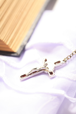 Isolated shot of rosary cross laid next to the bible