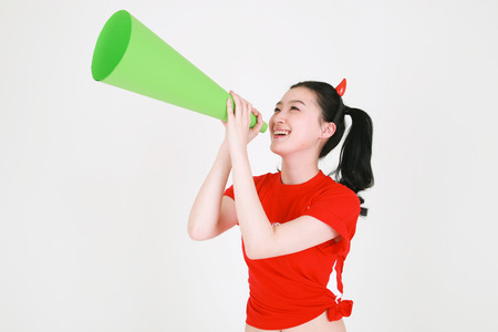 A Korean female soccer supporter with two ponytails posing with a cheering horn in studio