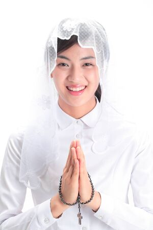 Close up shot of A female Asian wearing a mass veil praying with toothy smile as holding a rosary in hand