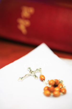 Close up shot of a brown rosary laid on the folded white mass veil with the bible in the back