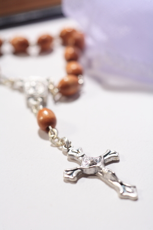 Close up shot of Rosary cross laid on the table